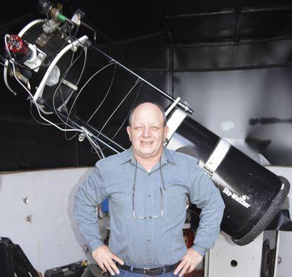 Víctor Buso frente a su telescopio en su casa de Rosario, Argentina.