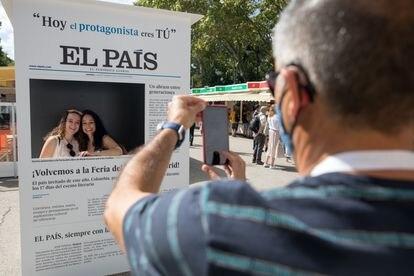 Dos visitantes de la Feria del Libro de Madrid se toman una foto con la portada de EL PAÍS.