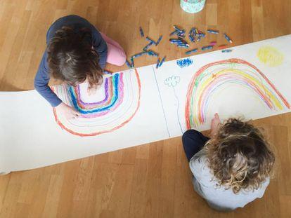 Dos niños pintan dos arcoíris en su casa durante el confinamiento.