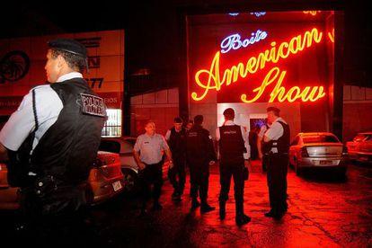 Un grupo de policías esperan fuera de un local nocturno en Brasilia (Brasil), este sábado.