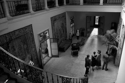 Vestíbulo del palacete de la calle de Muntaner, en una imagen de la película 'Blancanieves' rodada allí; las paredes vacías de cuadros están cubiertas por grandes tapices.