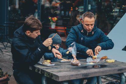 Dos padres comen con su hijo en su restaurante.