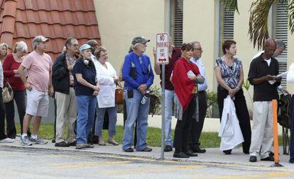 Varias personas esperan en fila para ejercer su derecho al voto en un colegio electoral en Miami.