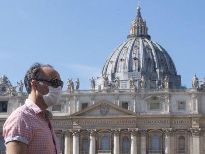 Un turista pasea con mascarilla por delante de la plaza de San Pedro, en el Vaticano.