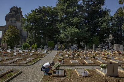 Una mujer coloca flores en la parte del cementerio de Bérgamo donde se enterró a todos los fallecidos por covid-19.