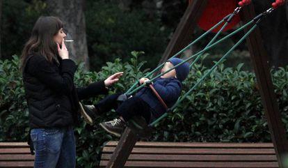 Una mujer fuma un cigarrillo ante un columpio ocupado por un niño en el parque del Retiro de Madrid
