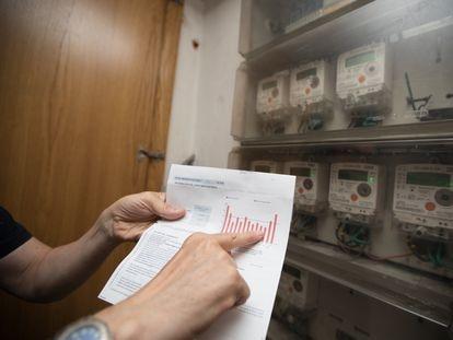 Un usuario muestra su factura junto al contador de luz en su domicilio en Madrid, en una foto de archivo.