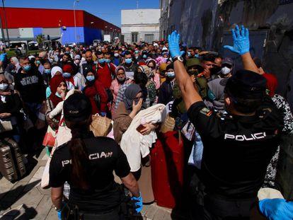 Una pareja de agentes del Cuerpo Nacional de Policía da instrucciones al grupo de 200 marroquíes que hacen  cola para poder pasar a Marruecos a través del paso fronterizo de Beni-Enzar de Melilla.