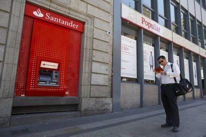 Un hombre mira su móvil ante dos oficinas de Santander y Popular.