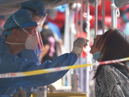 Trabajadores sanitarios efectúan una prueba del coronavirus a una residente de Pekín
