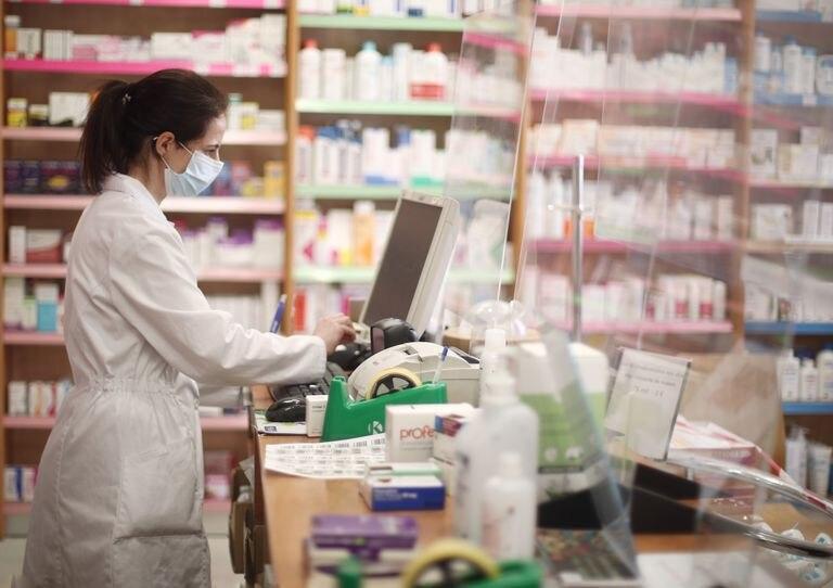 Una farmacéutica con mascarilla despacha en una farmacia.