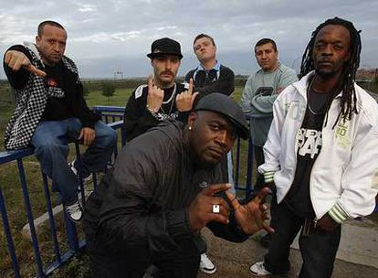 Figuras de los inicios y del momento actual del <i>rap</i> en Torrejón, con la base aérea al fondo. De izquierda a derecha, Randy, Cerroman 1/29, Blue Ice, Frank T, DJ Lara y Señor T Cee.