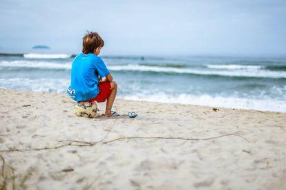 Un niño está sentado en la playa, mirando el mar.