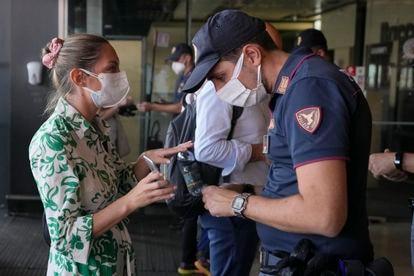 Un poliziotto controlla il certificato verde di una donna alla stazione ferroviaria di Milano Porta Garibaldi.