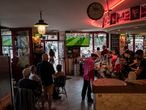 Customers inside a bar watch the Euro 2020 soccer championship group F match between France and Hungary, in Paris, France, Saturday, June 19, 2021. (AP Photo/Rafael Yaghobzadeh)