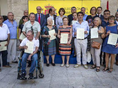 Los familiares de los represaliados con sus certificados este jueves en Valencia con la ministra de Justicia, Dolores Delgado.