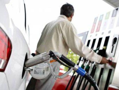 Un hombre reposta en una gasolinera.
