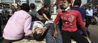 Los manifestantes retiran a los heridos de la plaza Ramsés, de El Cairo.