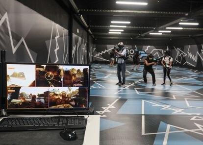 Varios jugadores, durante una partida de realidad virtual de 'Far cry' en Zero Latency. En la pantalla del ordenador, lo que ellos están viendo.