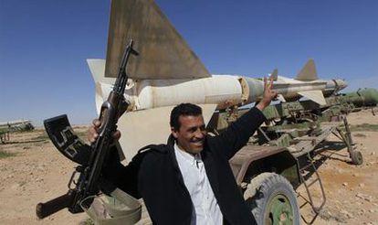 Un hombre hace el signo de la victoria ante un misil antiaéreo abandonado por los militares en una base cercana a Tobruk, en el este de Libia. Las ciudades de la parte oriental del país han festejado hoy el triunfo de la revuelta contra el dictador Muamar el Gadafi.