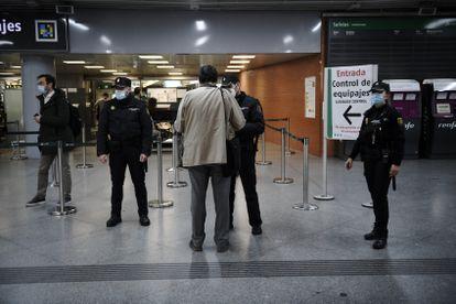 Varios agentes de la Policía Nacional controlan la documentación de los pasajeros en la estación de Atocha, en Madrid, el pasado jueves.