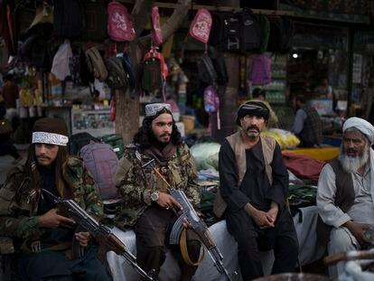 Guerrilleros talibanes descansan junto a dos vendedores de un mercado local de Kabul, este viernes.