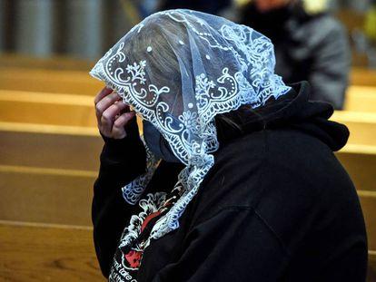 Una mujer reza en una iglesia.