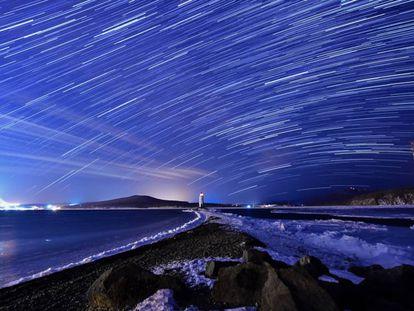 Lluvia de estrellas de las Gemínidas durante su pico, en el cielo nocturno sobre el faro de Tokarevsky en el cabo de Egersheld en la isla de Russky en el mar de Japón.
