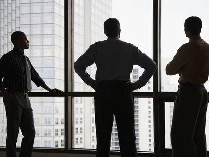 Tres ejecutivos frente a una ventana