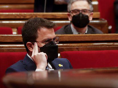 En primer plano, el 'president' Pere Aragonès, escucha al portavoz de JxCat, Albert Batet (fondo), durante el pleno del Parlament.