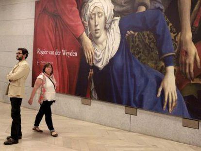 Dos espectadores junto al 'Descendimiento de la cruz' del flamenco Rogier van der Weyden, en el museo de El Prado.