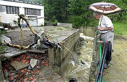 Un vecino del barrio de Narrondo, en Zumaia (Guipúzcoa), observa los destrozos causados por la riada.
