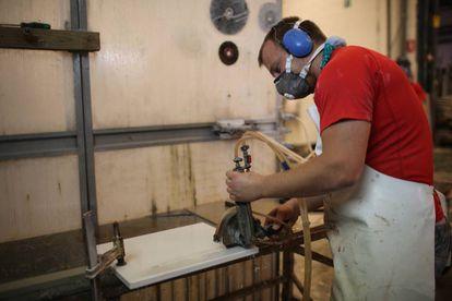 Un operario corta un bloque de cuarzo para encimera
