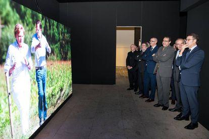 Alberto Núñez Feijóo, a la derecha, junto a Antonio Caño y varios cargos del grupo Prisa, el delegado del Gobierno en Galicia y el arzobispo observan una foto de Merkel y Rajoy en el Camino de Santiago.