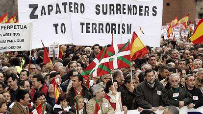 """Mariano Rajoy porta la segunda pancarta. Detrás, en inglés, se lee """"Zapatero se rinde al terrorismo""""."""