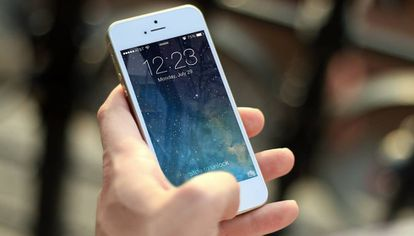 Un usuario de un teléfono de Apple, una de las empresas multadas en Italia por obsolescencia programada.