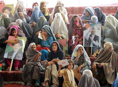 Un grupo de mujeres, algunas con <i>burka,</i> exhibe pancartas de Hamid Karzai durante un mitin en Kandahar.