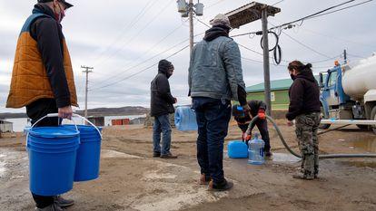 Un grupo de personas hace fila para recolectar agua de un camión cisterna el jueves.