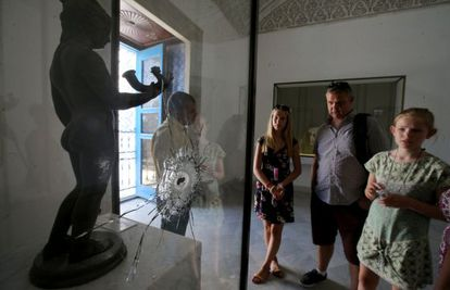 Una familia contempla, este martes en el Museo Nacional del Bardo, una obra tiroteada durante el atentado islamista del pasado marzo.