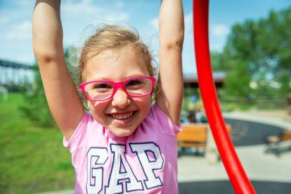 Una niña con gafas juega en un columpio.