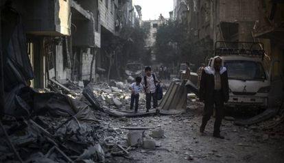 Dos niños y un hombre caminan entre los escombros en Duma, un distrito rebelde de Damasco (Siria), el 21 de octubre de 2015