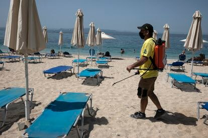 Un hombre desinfecta las hamacas de una playa próxima a Atenas, este sábado.