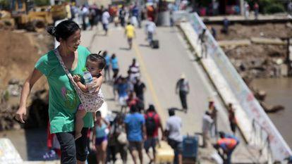 Los damnificados cruzan un puente destruido en Coyuca de Benítez (Guerrero)
