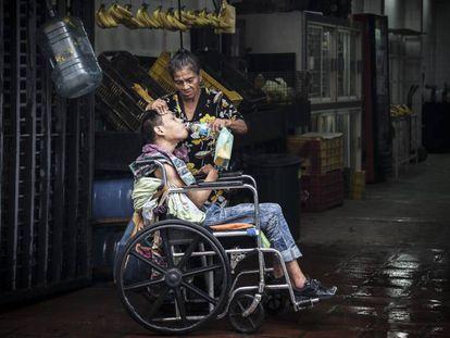 Una madre da de beber agua a su hijo postrado en una silla de ruedas en Caracas.