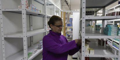 Una empleada de una farmacia toma medicinas de una estantería en Caracas.