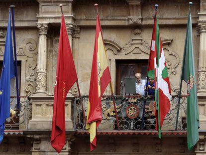 Dos operarios municipales instalan este jueves la ikurriña minutos antes del chupinazo de San Fermín.