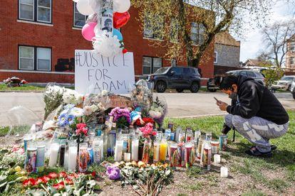 Una mujer se arrodilla frente a un altar en memoria de Adam Toledo, de 13 años, instalado cerca del callejón donde un policía le disparó en el vecindario de La Villita en Chicago.