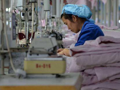 Una trabajadora cose en una empresa de Binzhou, en la provincia de Shandong (China), ropa que será exportada a Estados Unidos.