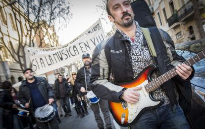Gustavo, en la marcha de músicos, puntea su guitarrra.