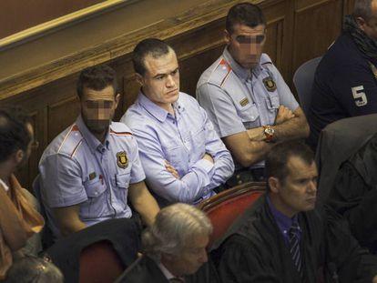 Ricardo Mateo, entre dos 'mossos', en un juicio contra los Casuals en 2012.